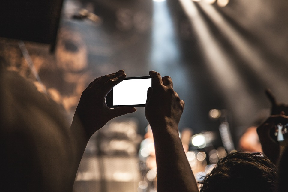 A person holding a smartphone at a concert.